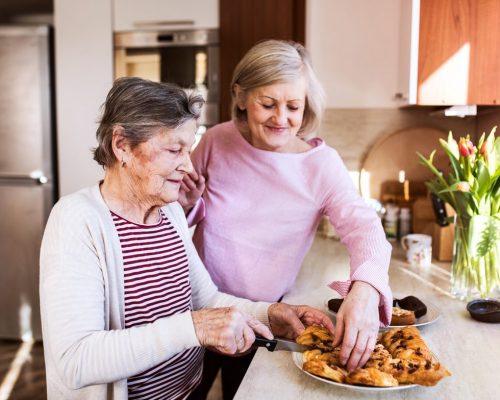 senior-women-preparing-food-in-the-kitchen-PEBZKPD